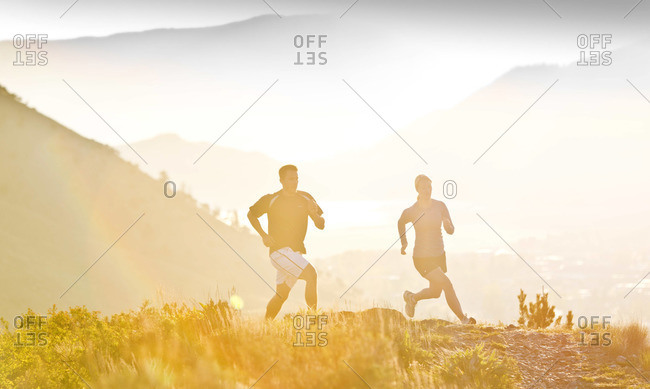 Silhouette of two persons running in landscape