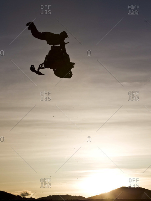 Snowmobile rider jumping above landscape
