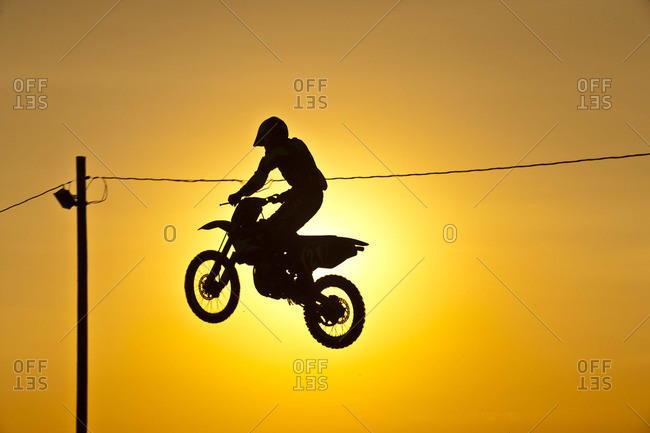 Silhouette of jumping motorcyclist