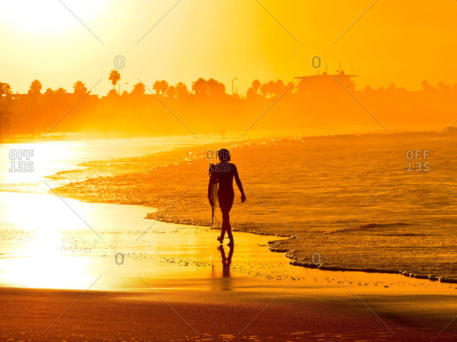 Silhouette of a person walking with surfboard on beach