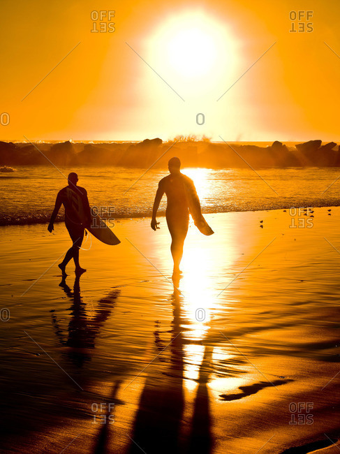 Two guys walking on sunlit beach with surfboards