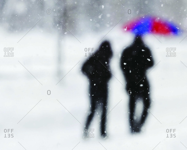 Silhouette of two persons walking in snow