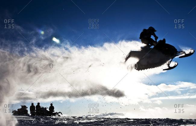 Snowmobile rider jumping