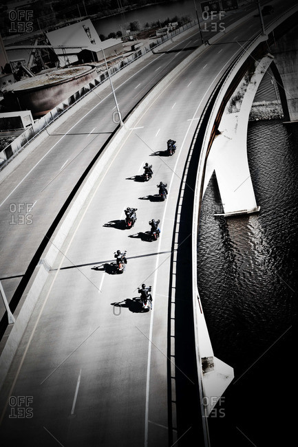 Group of motorcyclists riding on the bridge