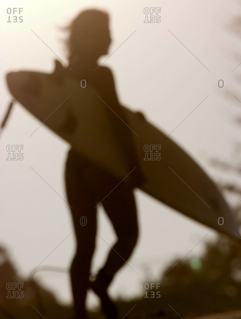 Silhouette of a girl walking with surfboard