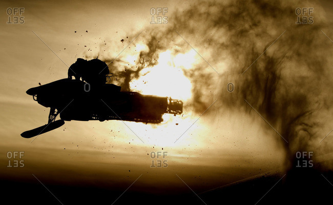 Snowmobile rider jumping against sky