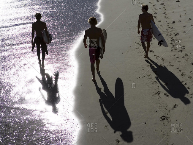 Three surfers walk with surfboards on seashore