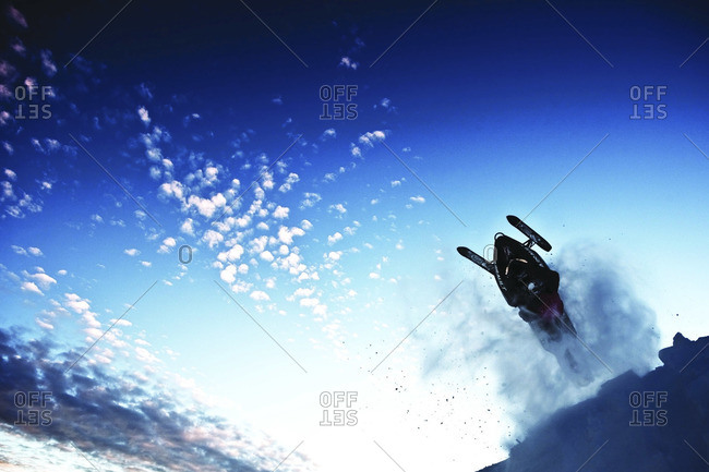 Snowmobile rider jumping against blue sky