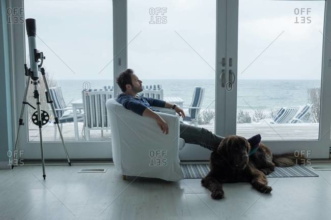 A young man relaxes with his dog at a beach house