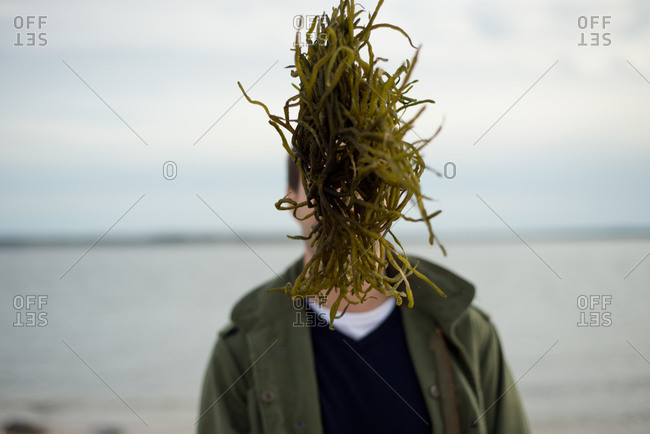 Portrait of a man with a green underwater plant obscuring his face