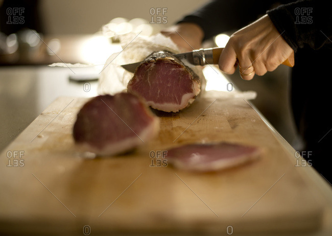 Woman slicing cured meat