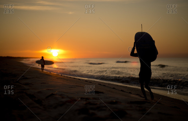 Surfers walking on the beach during sunset
