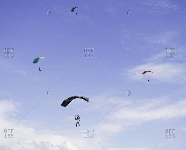 Four skydivers parachuting down