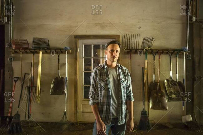 A man standing in a barn with farm equipment stored around the walls, Catskills