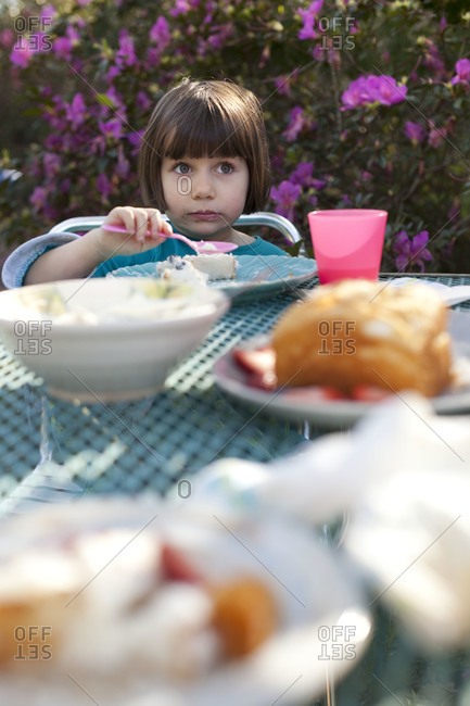 Young girl eating a cake at picnic