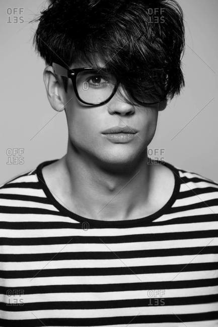 A black and white close-up studio portrait of a stylish handsome man in striped shirt wearing glasses