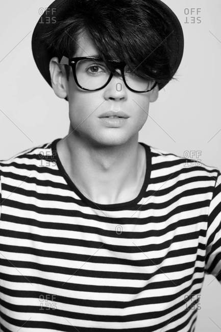 A black and white close-up studio portrait of a stylish handsome man in striped shirt wearing glasses and hat