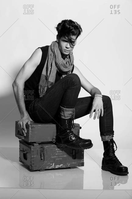 A black and white studio portrait of a stylish handsome man in black shirt and skinny black jeans with scarf, rockabilly style