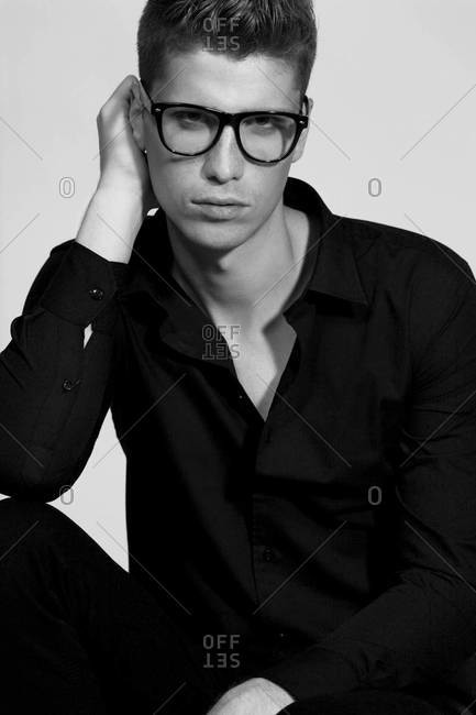 A black and white studio portrait of a stylish handsome man in black shirt wearing glasses
