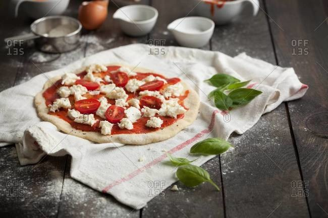 Stretched and uncooked pizza dough with tomato sauce, mozzarella and cherry tomatoes on a kitchen towel