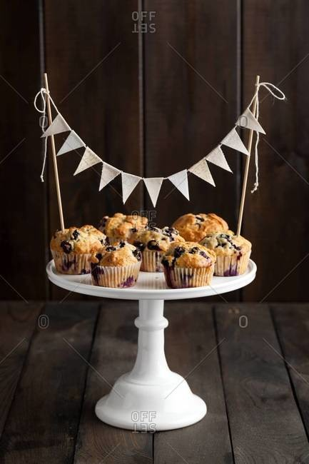 Freshly baked blueberry muffins served on a white cake stand and decorated with a bunting cake topper