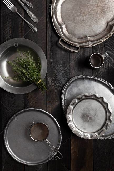 Assorted vintage cutlery, metal trays, a bunch of fresh thyme on a metal plate, sifter and a metal jug