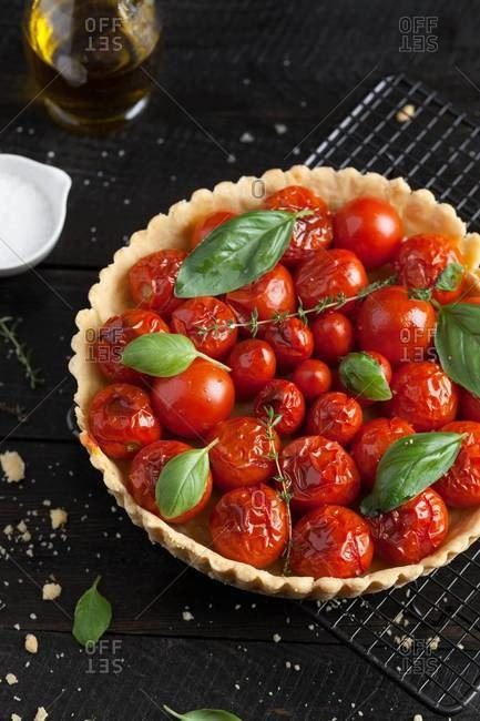 Cherry tomato tart with fresh basil leaves and thyme served on a cooling rack