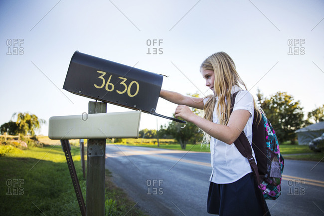 Young girl checking letter box