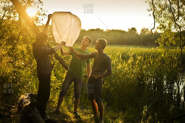Men launching floating lantern outdoors