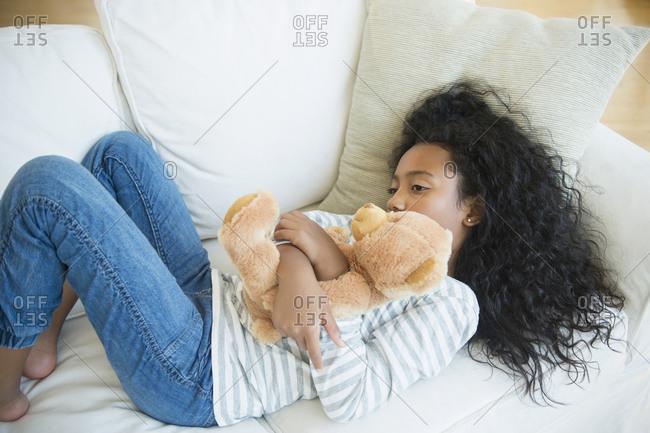 Girl hugging teddy bear on sofa