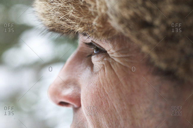Close up of Man wearing furry hat in snow