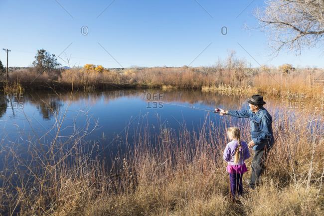 Senior man and granddaughter watching calm lake