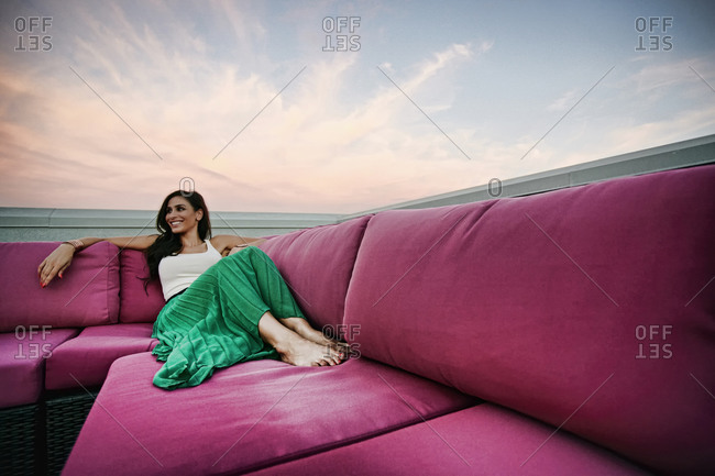 Woman relaxing on sofa outdoors
