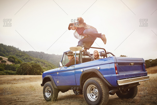 Man jumping from truck in rural landscape