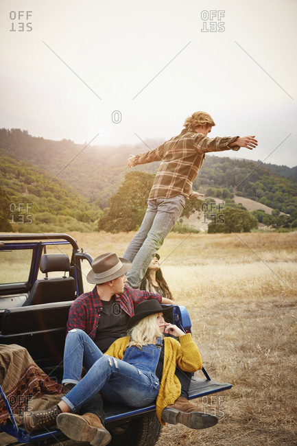 Man jumping off truck in rural landscape