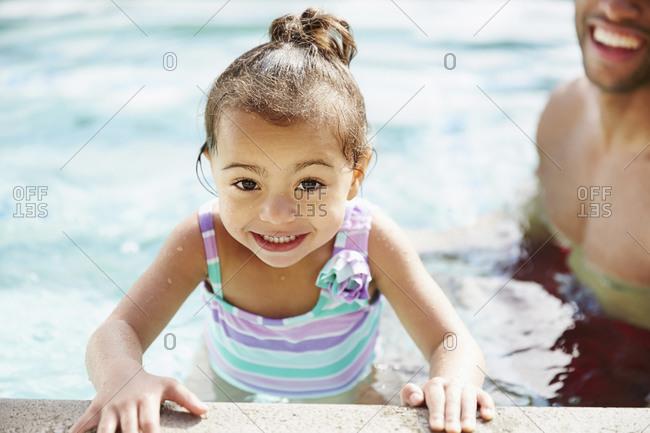 Father teaching daughter to swim in pool