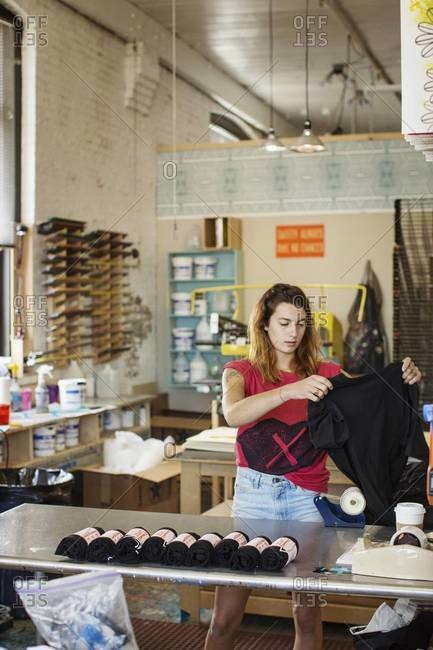 Young woman unrolling t-shirts for screen printing