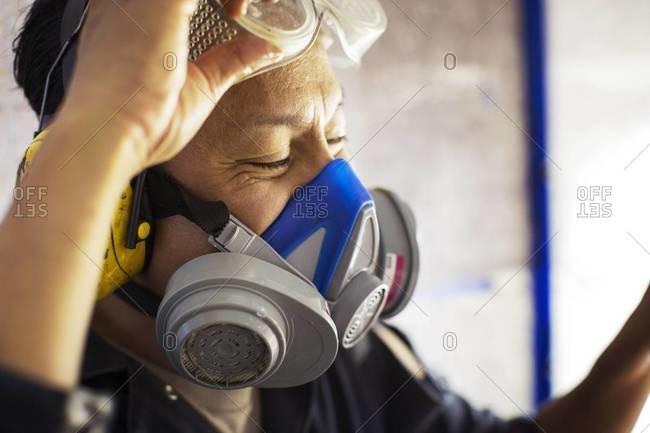 Close up of Asian man lifting his goggles and wearing respirator