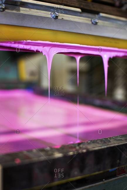 Close up of pink paint on screen and squeegee