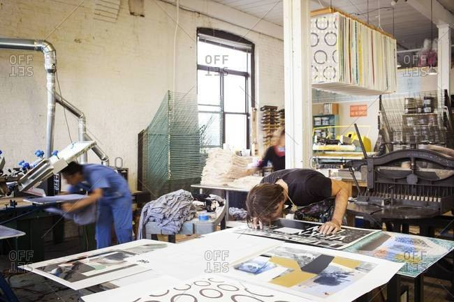 Young man checking the quality of screen print