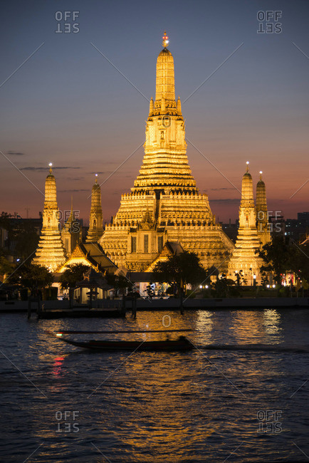 A longtail river boat passes in front of the Wat Arun temple at dusk in Bangkok
