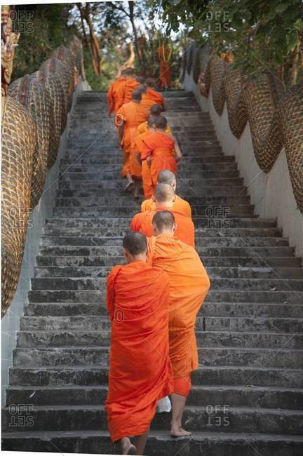 Monks climbing stairs in a row