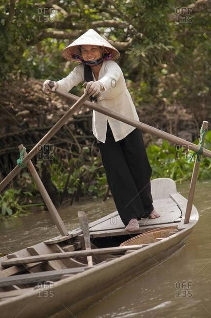 "MEKONG RIVER DELTA, VIETNAM - January 26, 2012: A woman wearing a ""non la"" conical hat rows a sampan boat in a canal near Cai Be"