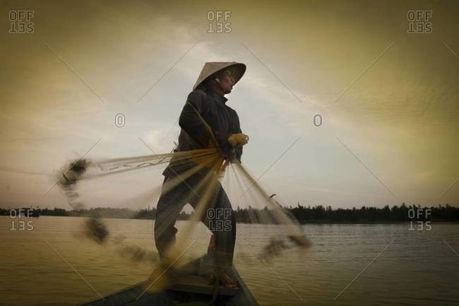 THU BON RIVER, VIETNAM - January 27, 2012: A fisherman throws his cast net into the Thu Bon River at sunset near Hoi An