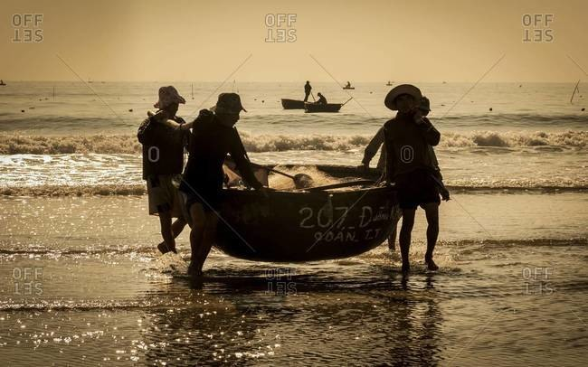 CHINA BEACH, VIETNAM - JANUARY 27, 2012: Fishermen carry a basket boat onto China Beach near Danang