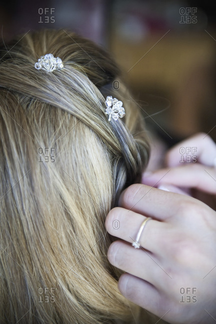 A bride having her hair braided and accessorized with hair pins.