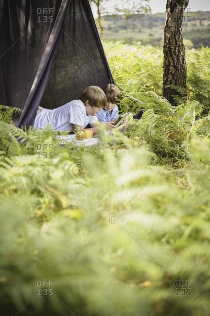 Two boys lying under a canvas shelter