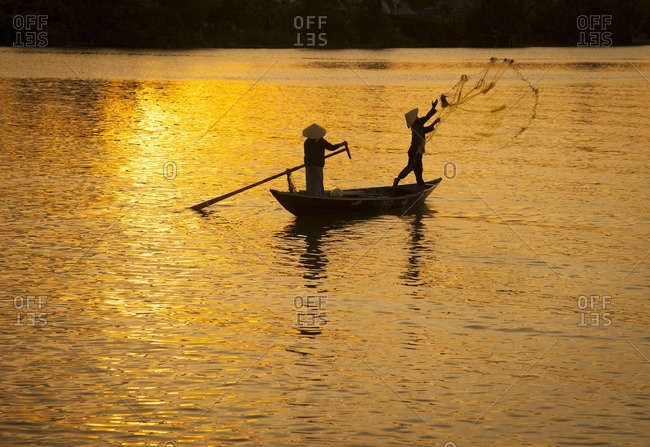 A fisherman throws his cast net into the Thu Bon River at sunset near Hoi An, Vietnam