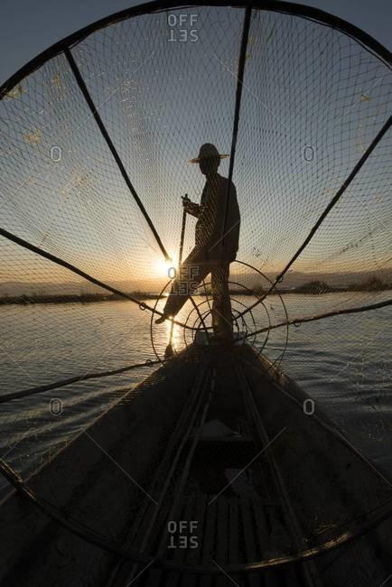 Silhouette of leg rowing fisherman on the Inle Lake, Myanmar