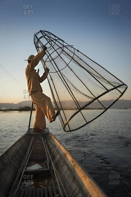 Leg rowing fisherman casting his net on the Inle Lake, Myanmar
